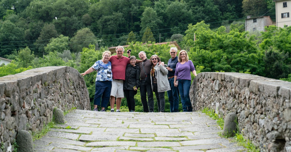 Group of friends smiling on a bridge in Tuscany